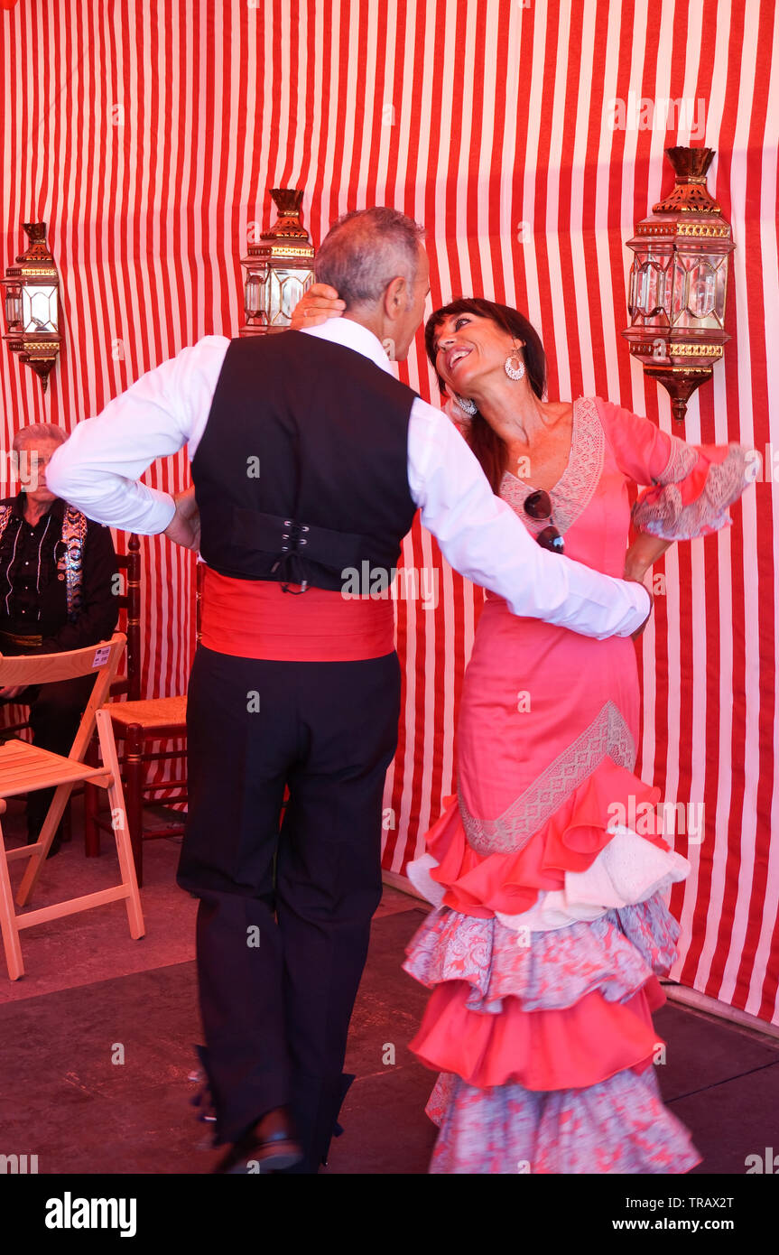 Torrevieja, Spain - June 1, 2019: Couple of mature people in traditional spanish clothe dancing together on Sevillian fair Stock Photo