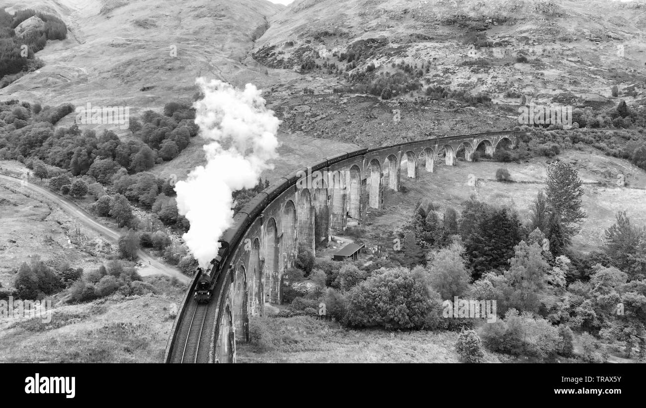 Steam Train crossing the Glenfinnan Viaduct, aerial view by drone, black and white filter - Scotland, UK - Stock Image