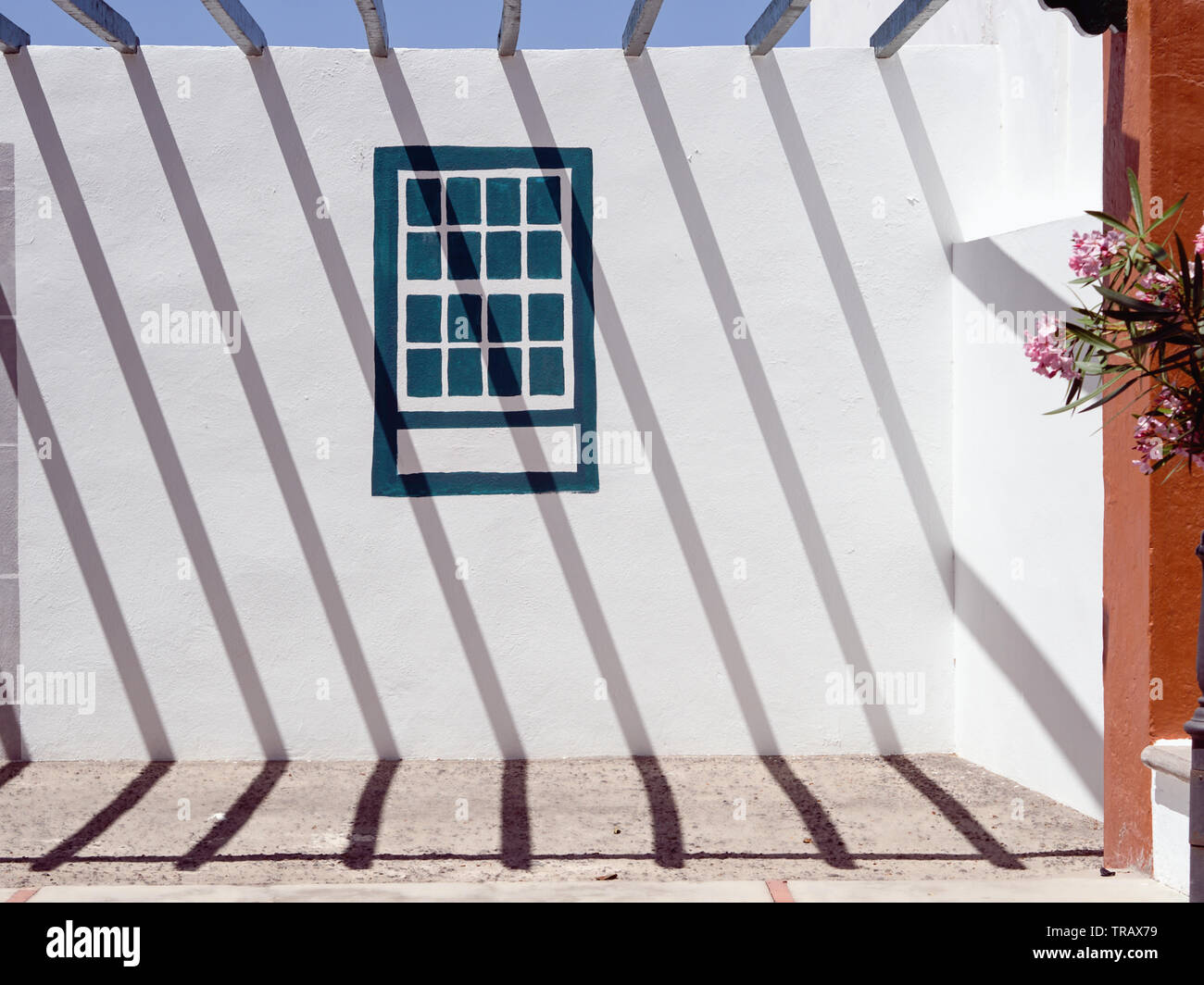 strong shadows of a metal grid cast a graphic pattern on a white wall diagonally from top left to bottom right, in the middle of the wall a window is - Stock Image