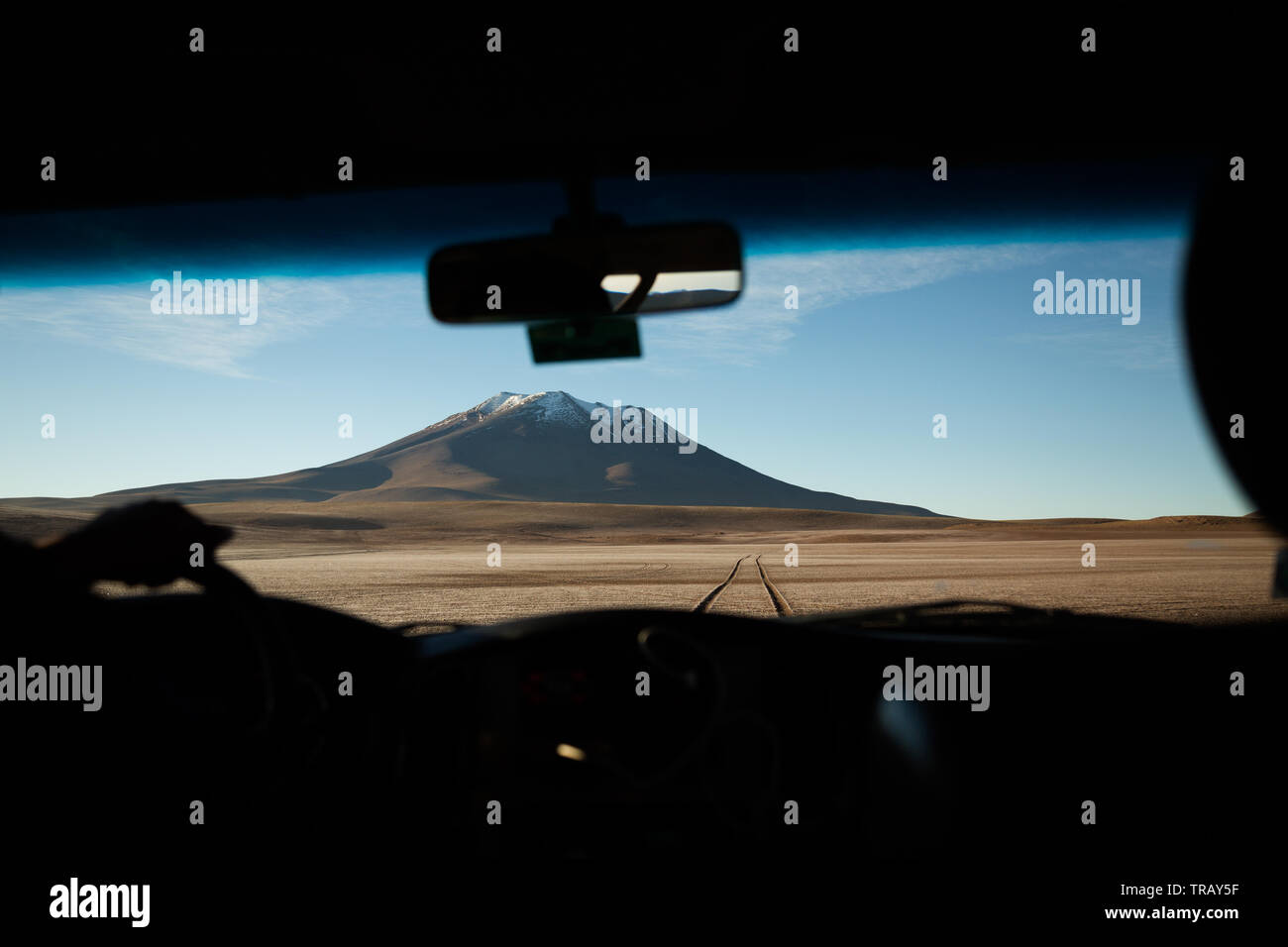 Driving on dirt track toward a volcanic peak on the Bolivian altiplano - Stock Image