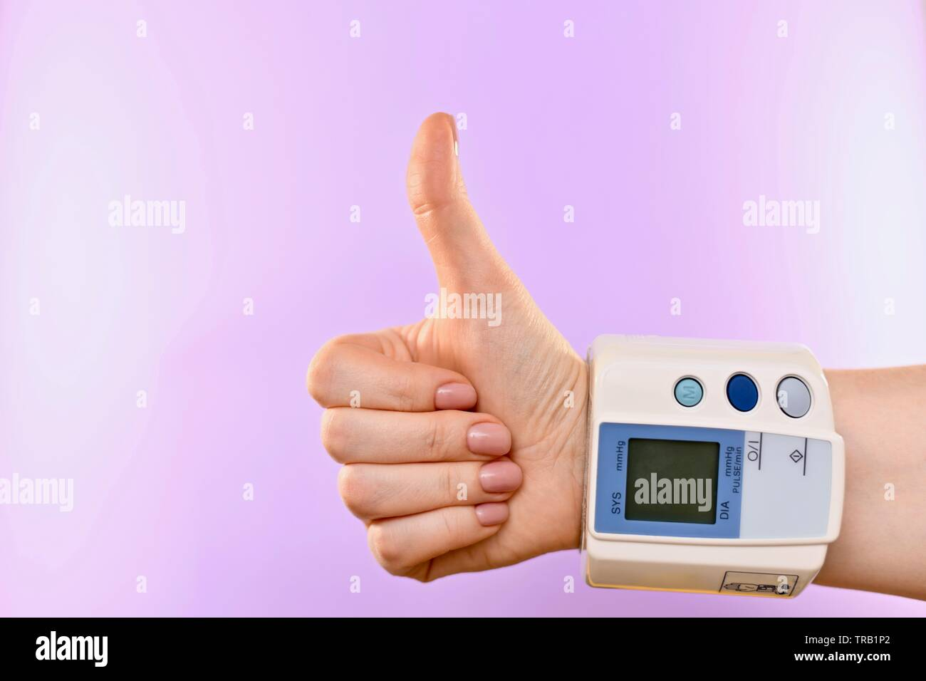 Arm and blood pressure monitor, buttoned at the wrist. In the center, from the bottom right corner. On a purple background. There are no indicators on - Stock Image