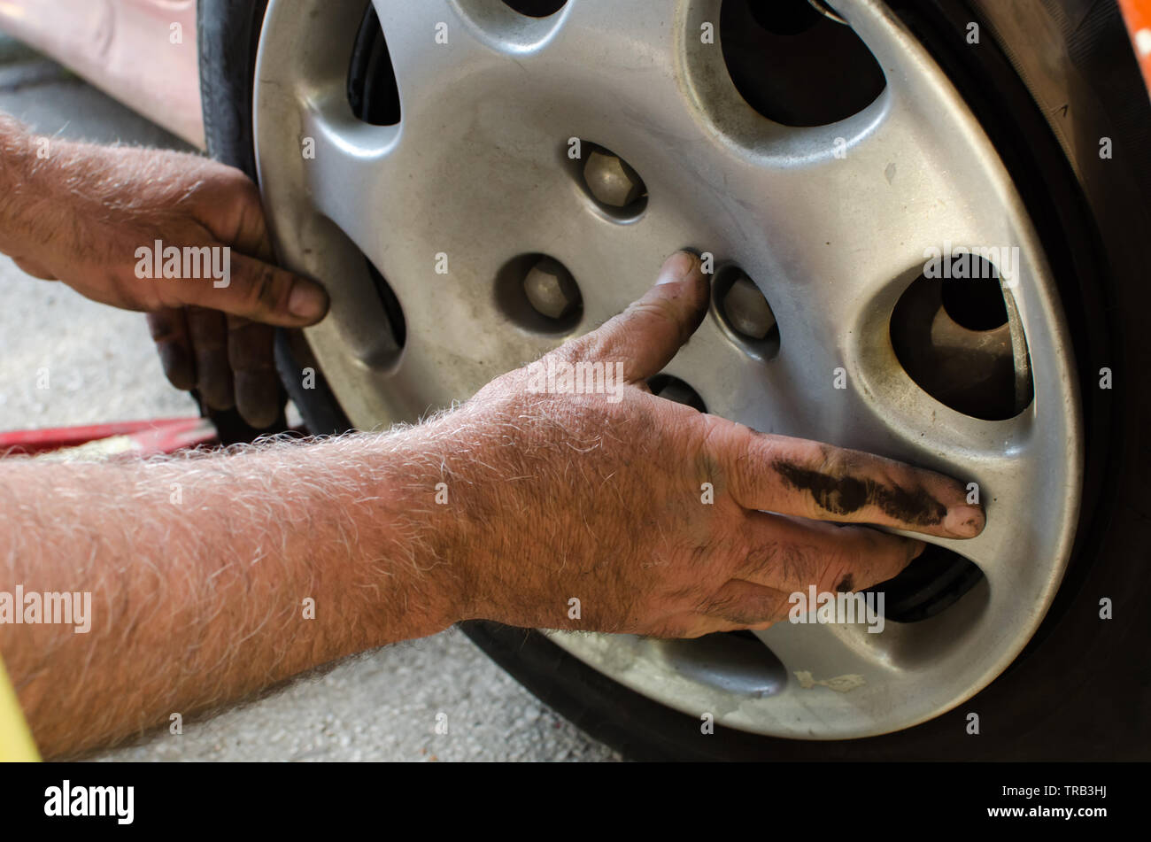 Mechanic with dirty hands replacing the plastic wheel cover after fixing tires, extreme close up, selective focus - Stock Image