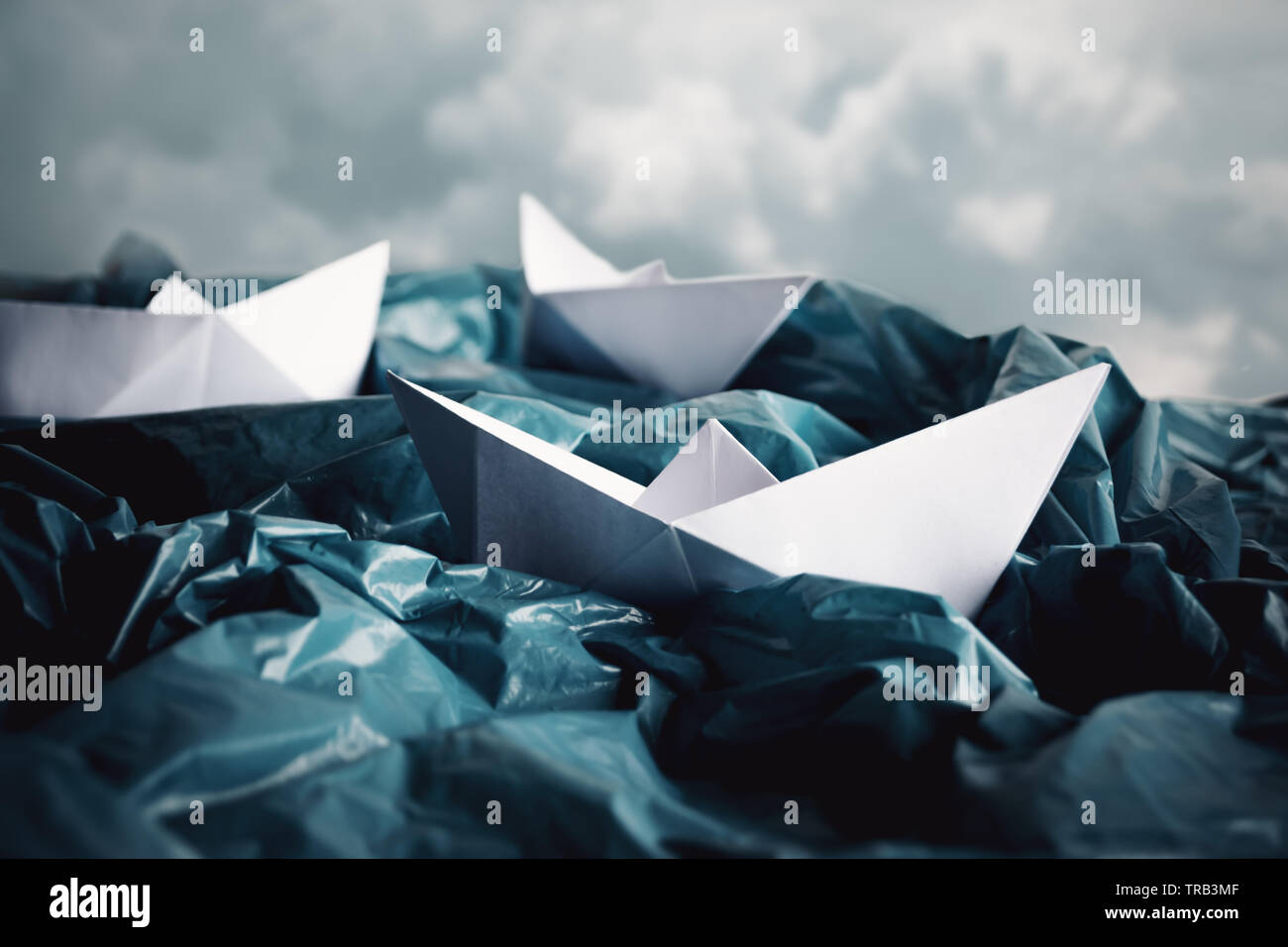 Concept of ocean pollution with plastic. Paper boats in stormy sea made of plastic bags. Creative representation of plastic ocean. - Stock Image