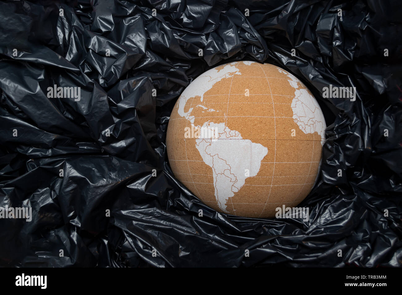 Cork globe representing planet Earth among black plastic bags, sinking. Ocean plastic pollution problem concept. - Stock Image