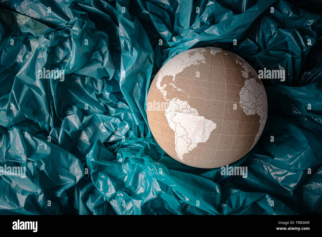 Cork globe sinking in blue plastic ocean. Creative concept of ocean pollution with plastic. Copy space, flat lay, horizontal. - Stock Image