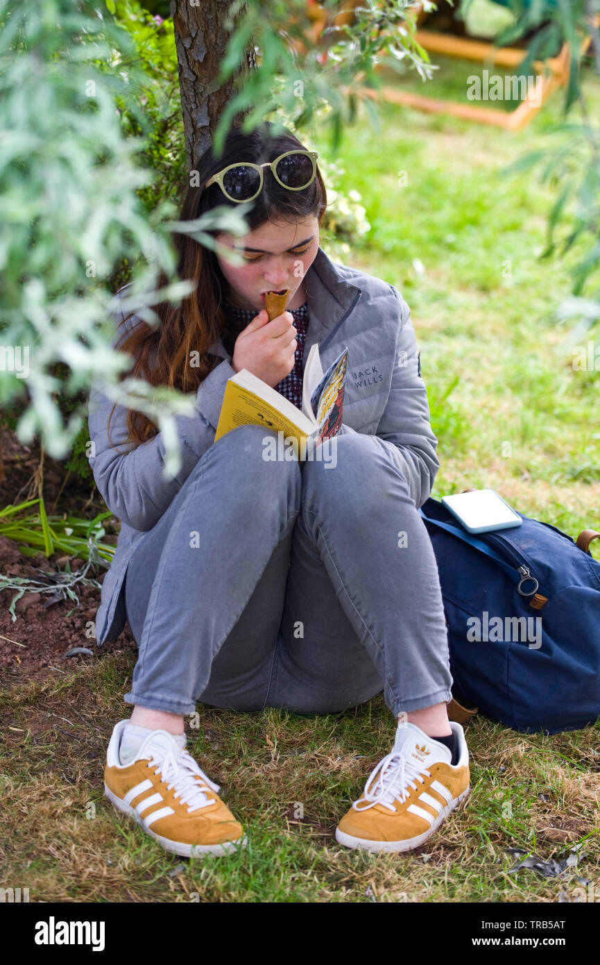 Young woman reading book and eating ice cream sitting under a tree at Hay Festival Hay on Wye Powys Wales UK - Stock Image