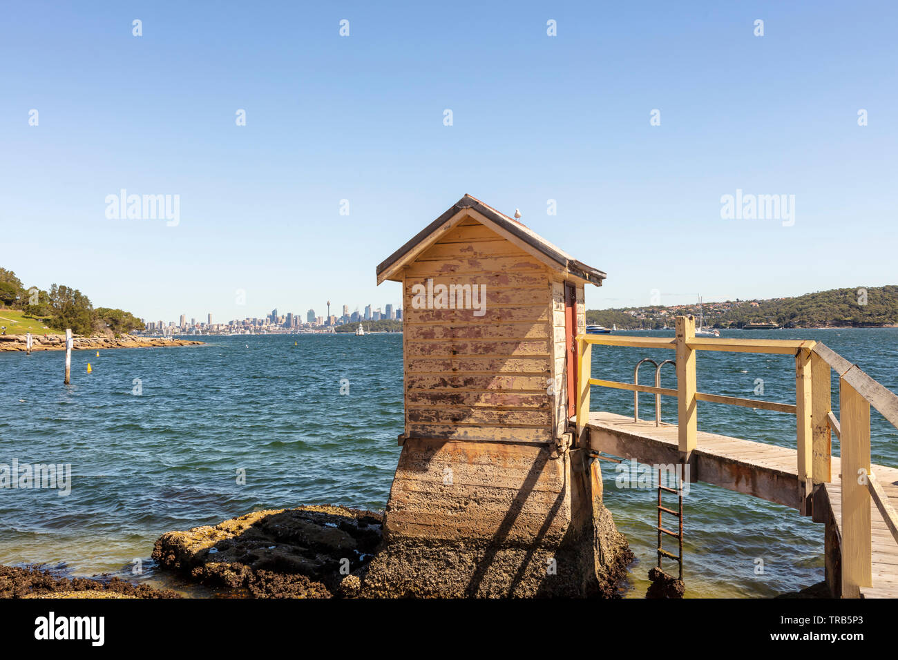 Vintage beach hut with peeling paint and small jetty on Camp Cove beach near Sydney, Australia. - Stock Image