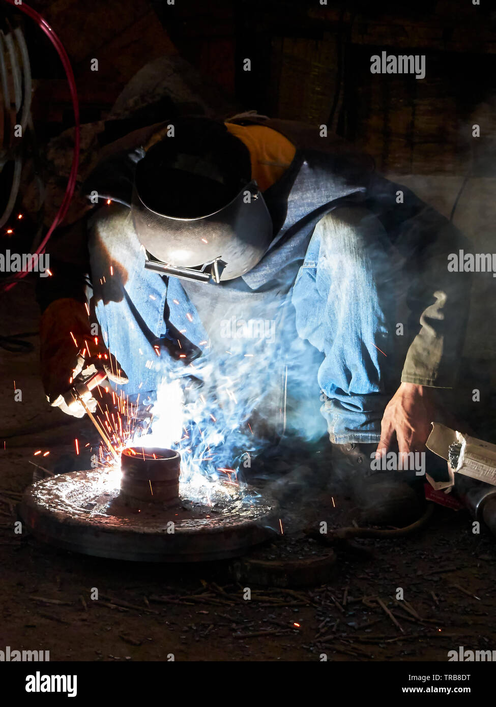 Close-up of a man dressed in jeans does a welding job in a dark place with sparks flying around, seen in the Philippines - Stock Image