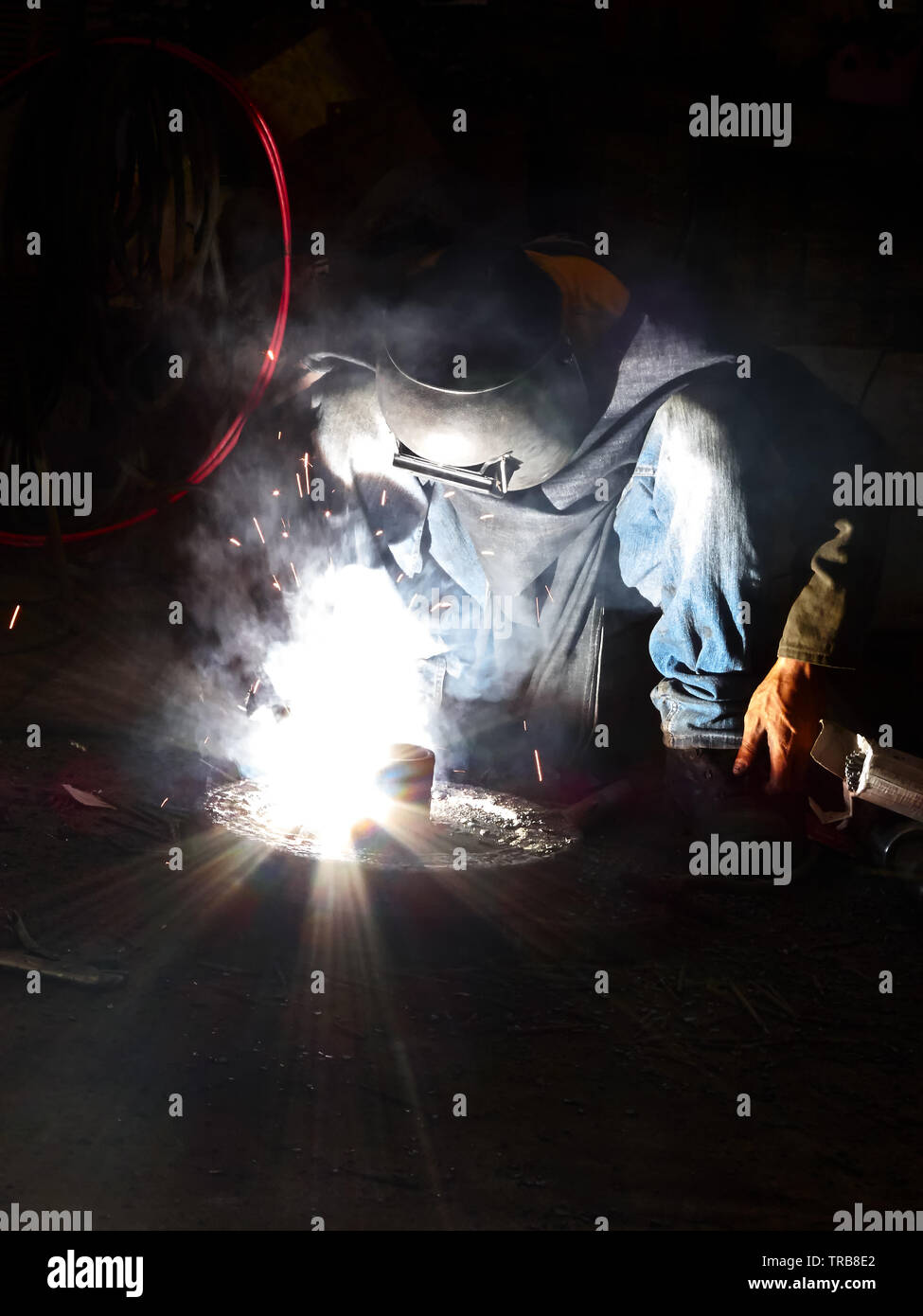 Close-up of a man dressed in jeans doing a welding job with sparks flying around, seen in the Philippines Stock Photo