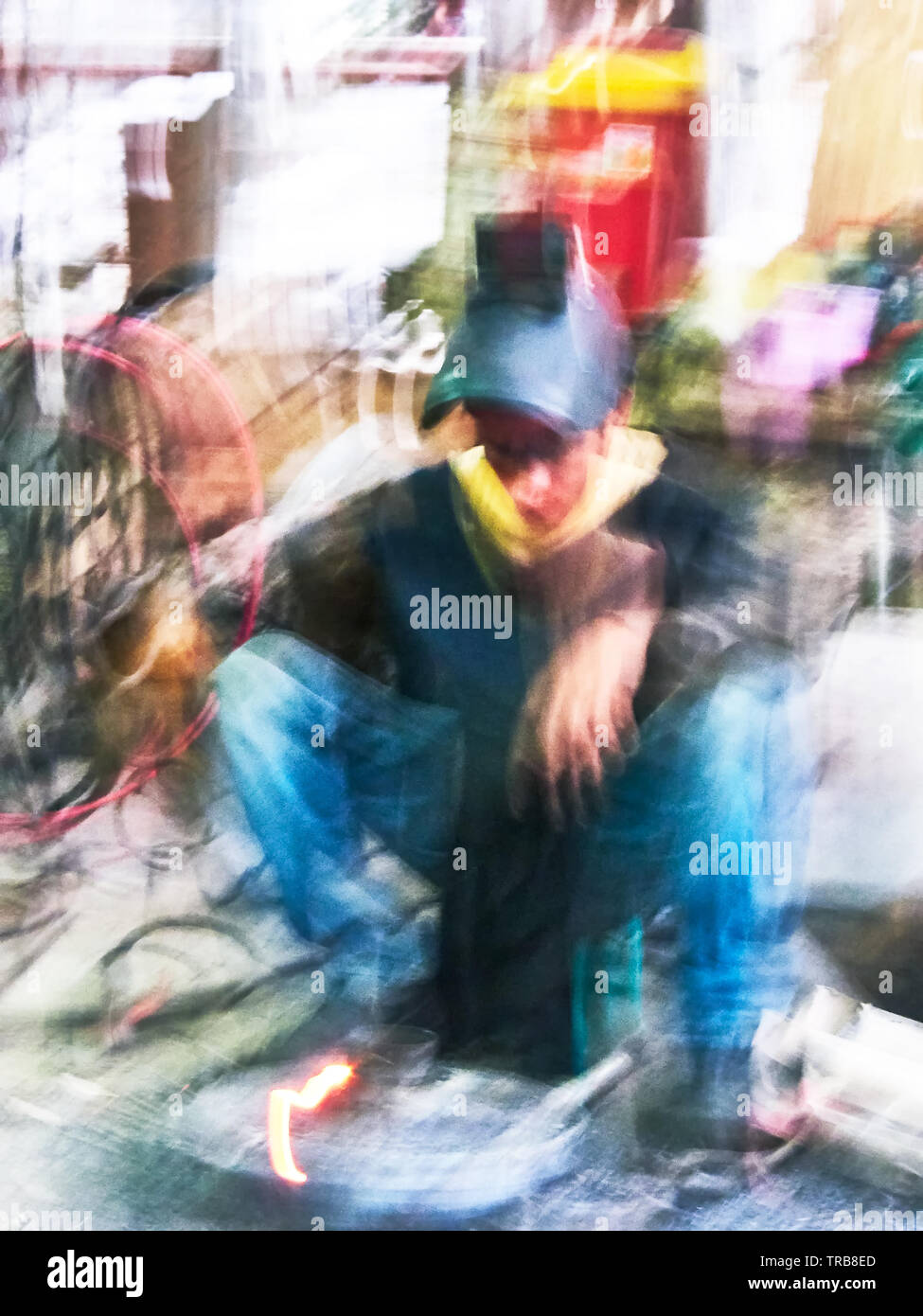 Abstract colorful picture of a man dressed in jeans doing a welding job in Asia - Stock Image