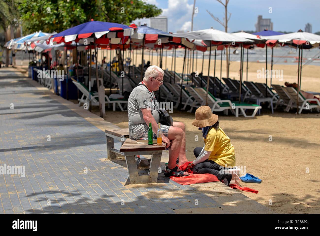 Thailand beach massage. Thai Masseuse with Caucasian customer at Pattaya beach, Southeast Asia - Stock Image