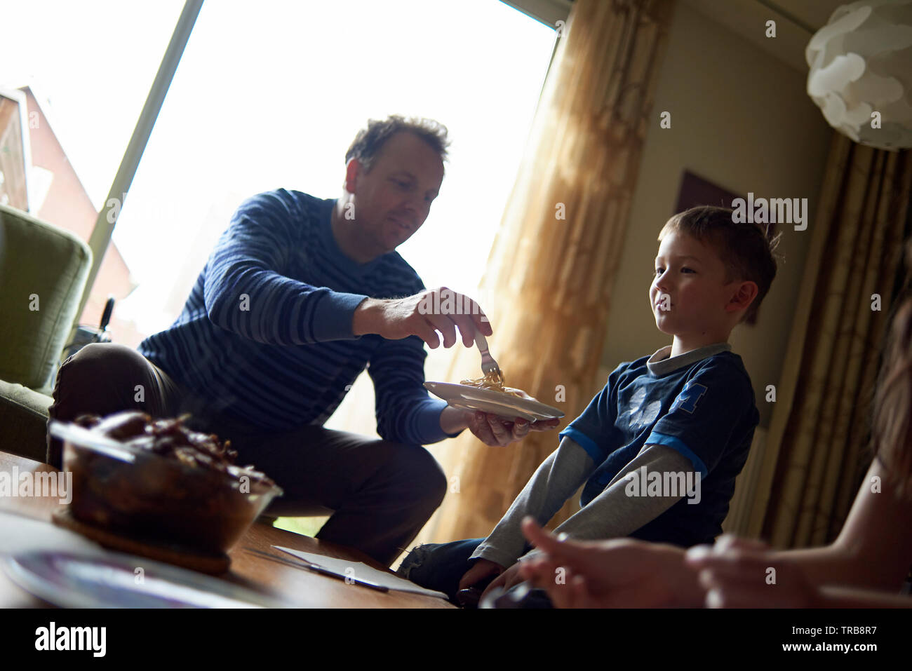 Father helping his cute young son to eat his lunch in the living room - Stock Image