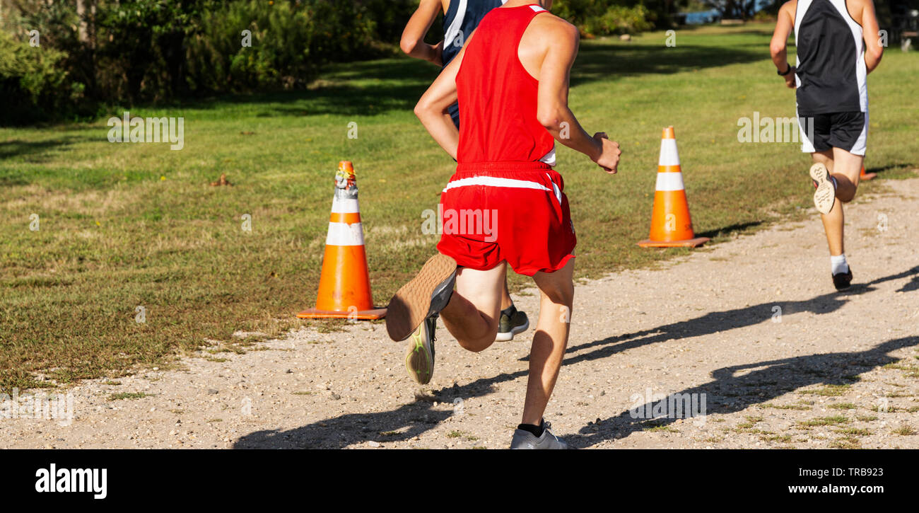 A high school boy running in a cross counrty race on a gravel path with the sun at his back making a large shadow in front. Stock Photo