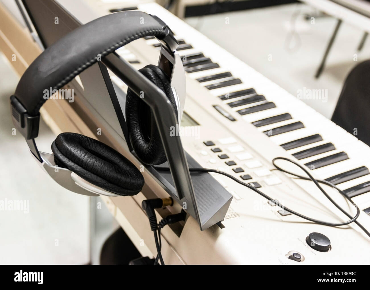 Headphones are resting on an electric piano ready to record music. - Stock Image