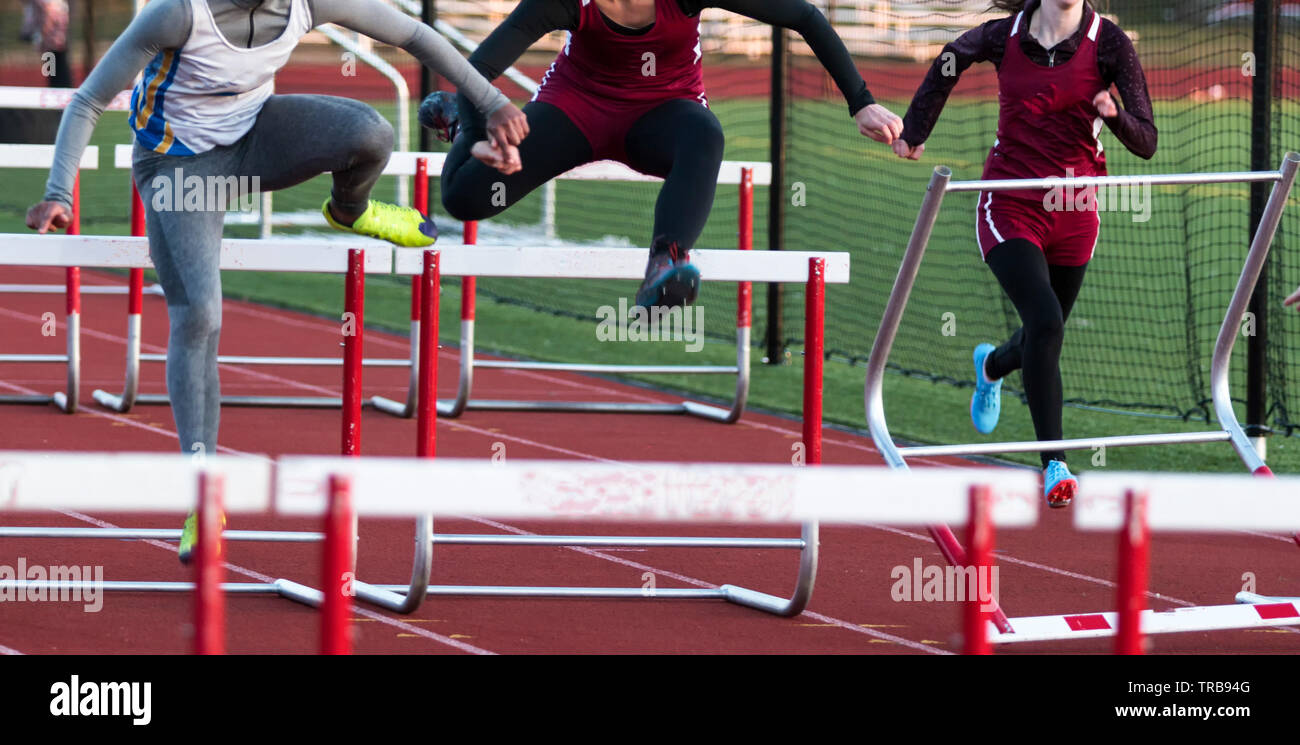 A high school hurdle race is run outdoors in the old early spring with girls hitting the hurdles and wearing spaned and long sleeves. - Stock Image