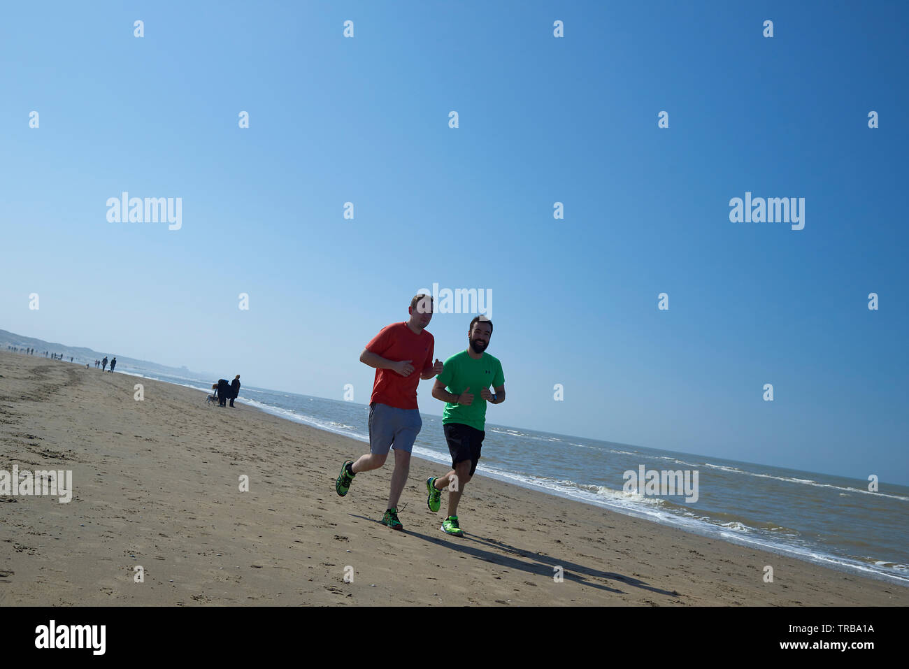 Two adult men running along the waterside at the beach in bright sunshine - Stock Image