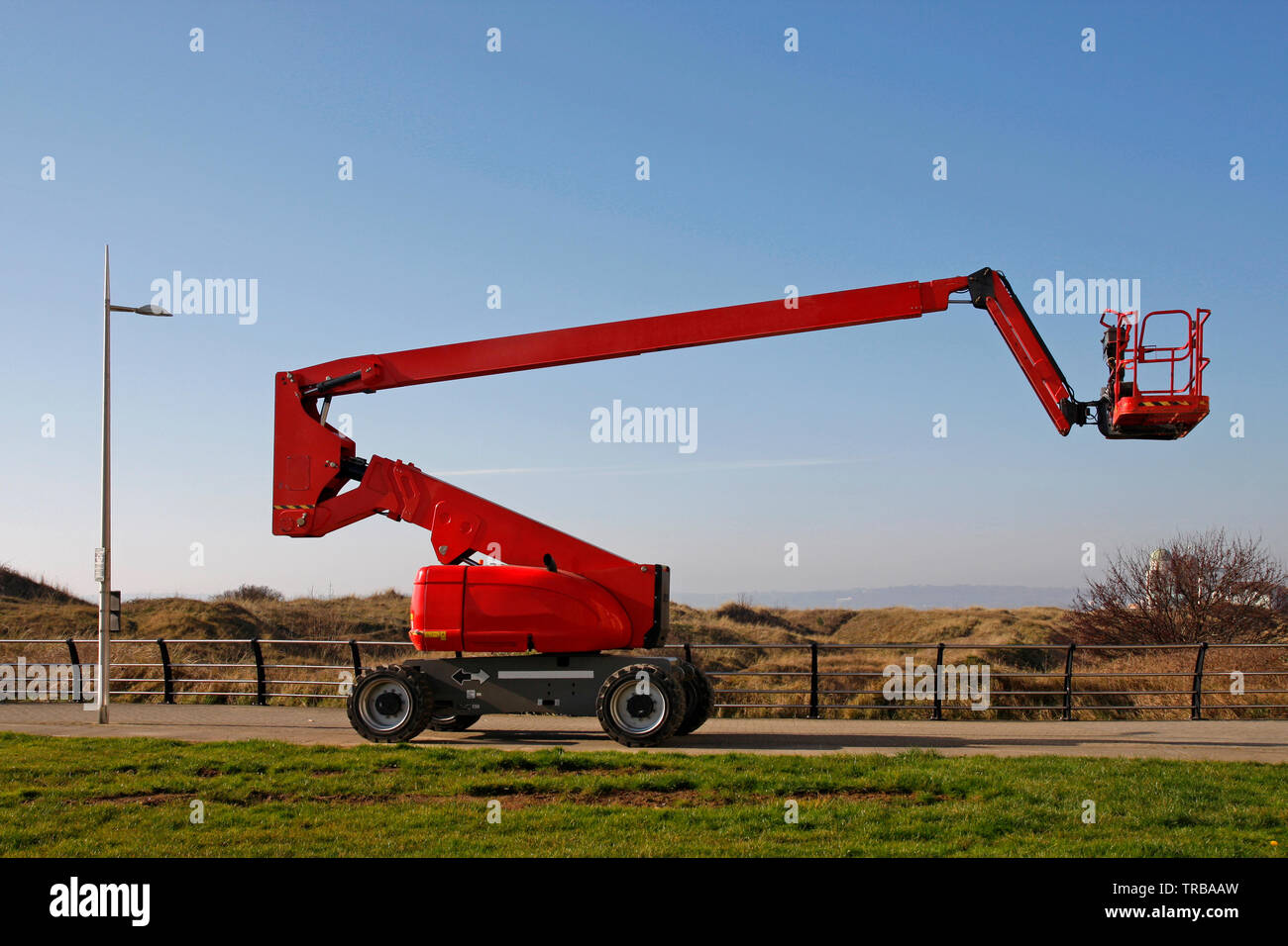 Orange cherry picker, side view against a blue sky - Stock Image