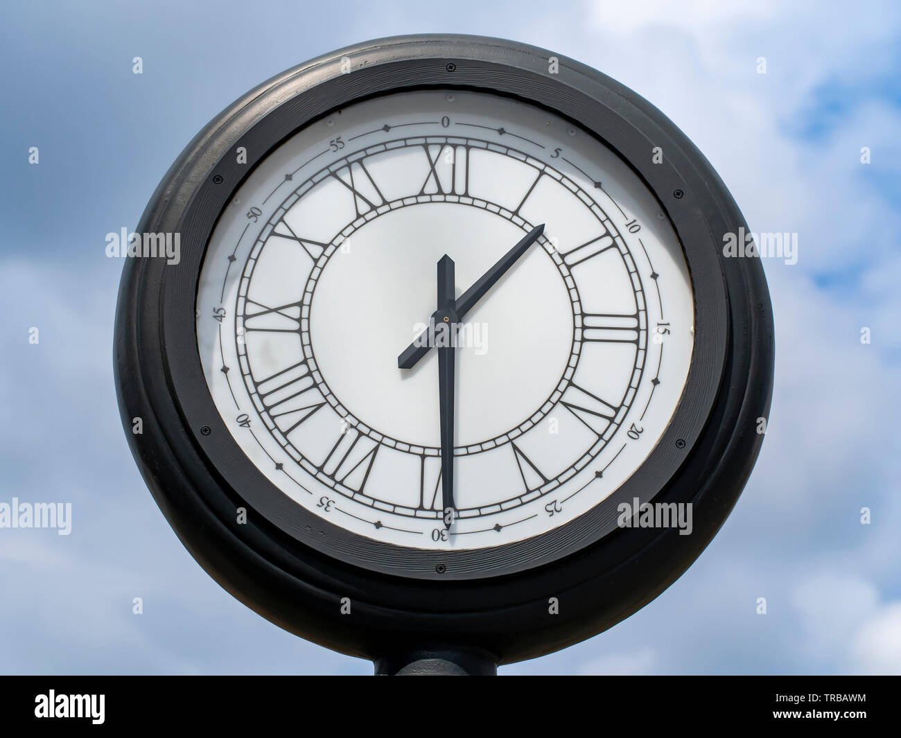 What time is it ? Half past one !.. Lunch break time. We need to eat something. Order lunch from restaurant. Street clock view during the sunny spring - Stock Image