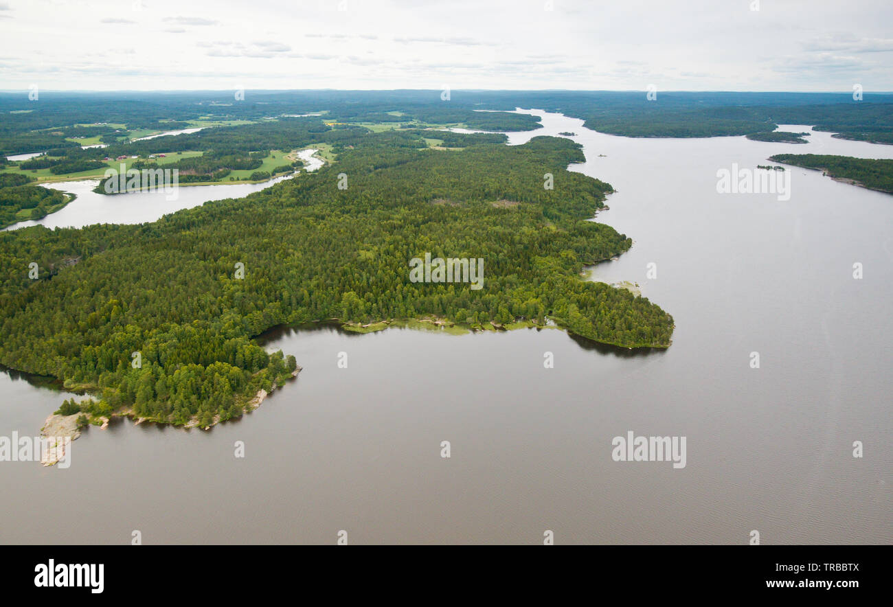 Aerial view over a part of the lake Vansjø in Østfold, Norway. Vansjø is the largest lake in Østfold. The bay in lower center is called Virebukt, and it is called the heart of the lake. The view is towards northeast. The open water in the lower right is called Storefjorden. The forested landscape in the center is called Holmelandet. June, 2006. - Stock Image