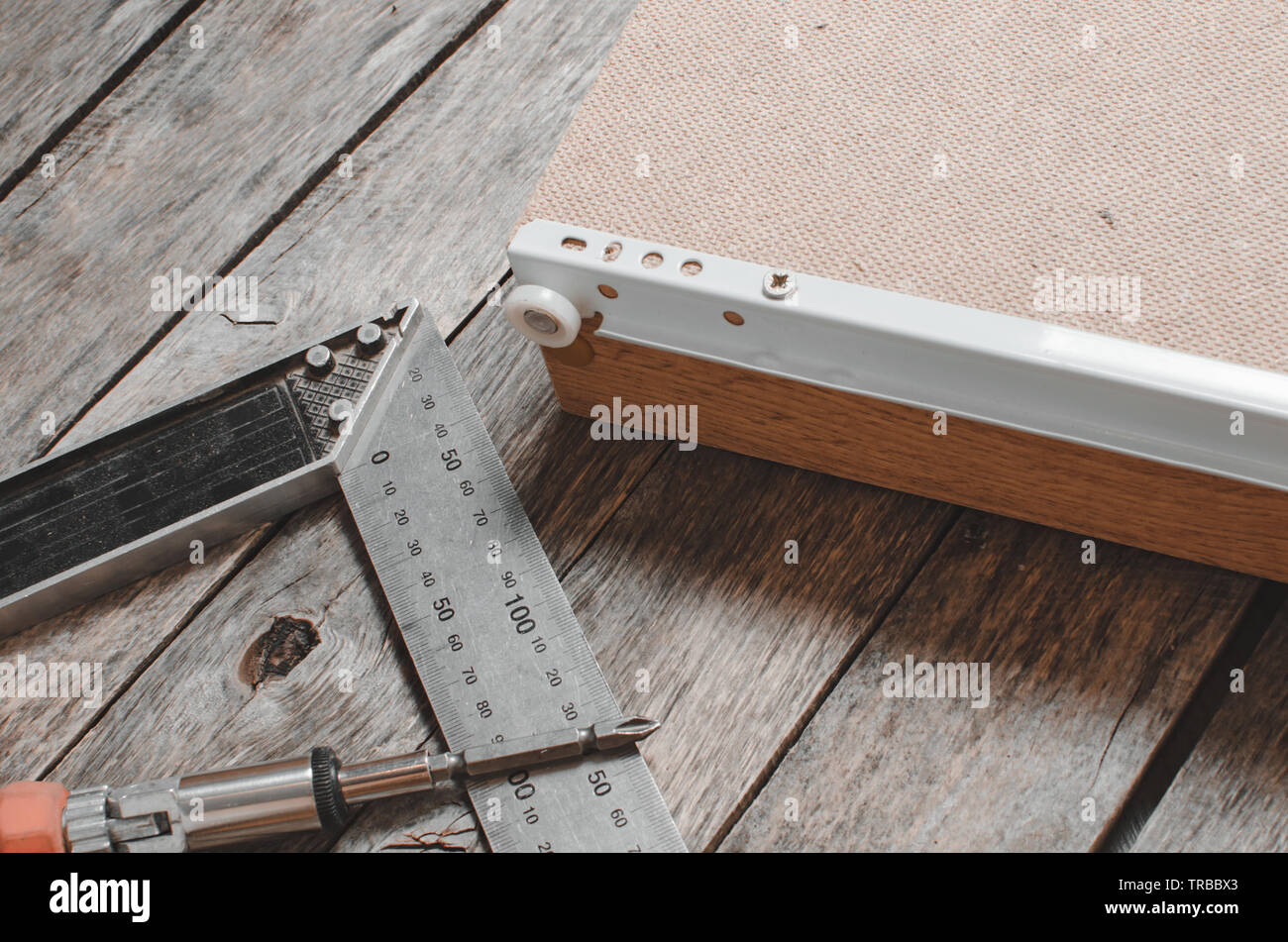 Screwdriver metal measuring corner and assembled furniture box with screwed guides. - Stock Image