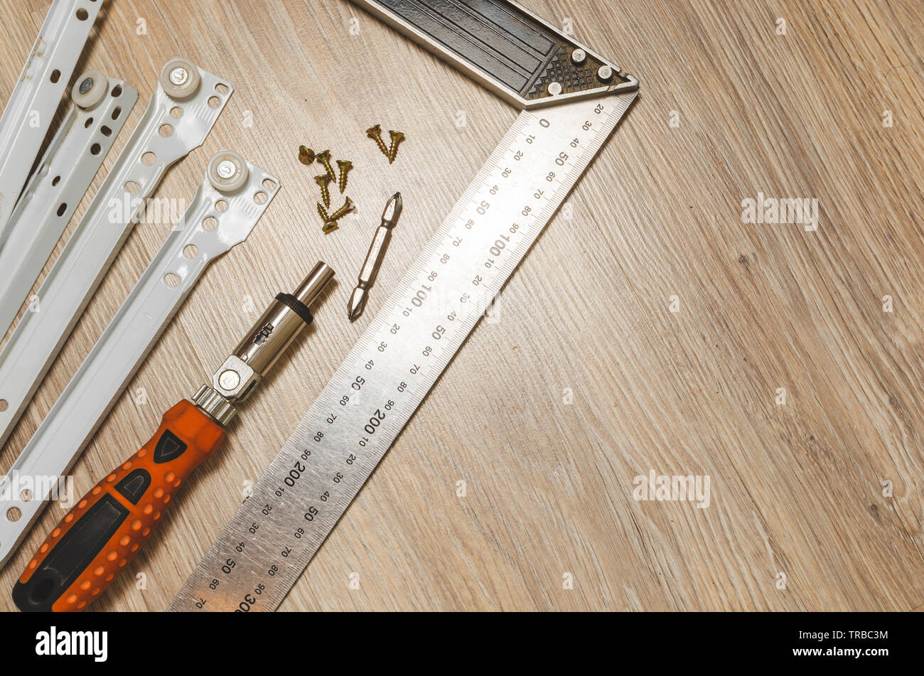 Screwdriver, metal and measuring the area and furniture guides. Furniture accessories. - Stock Image