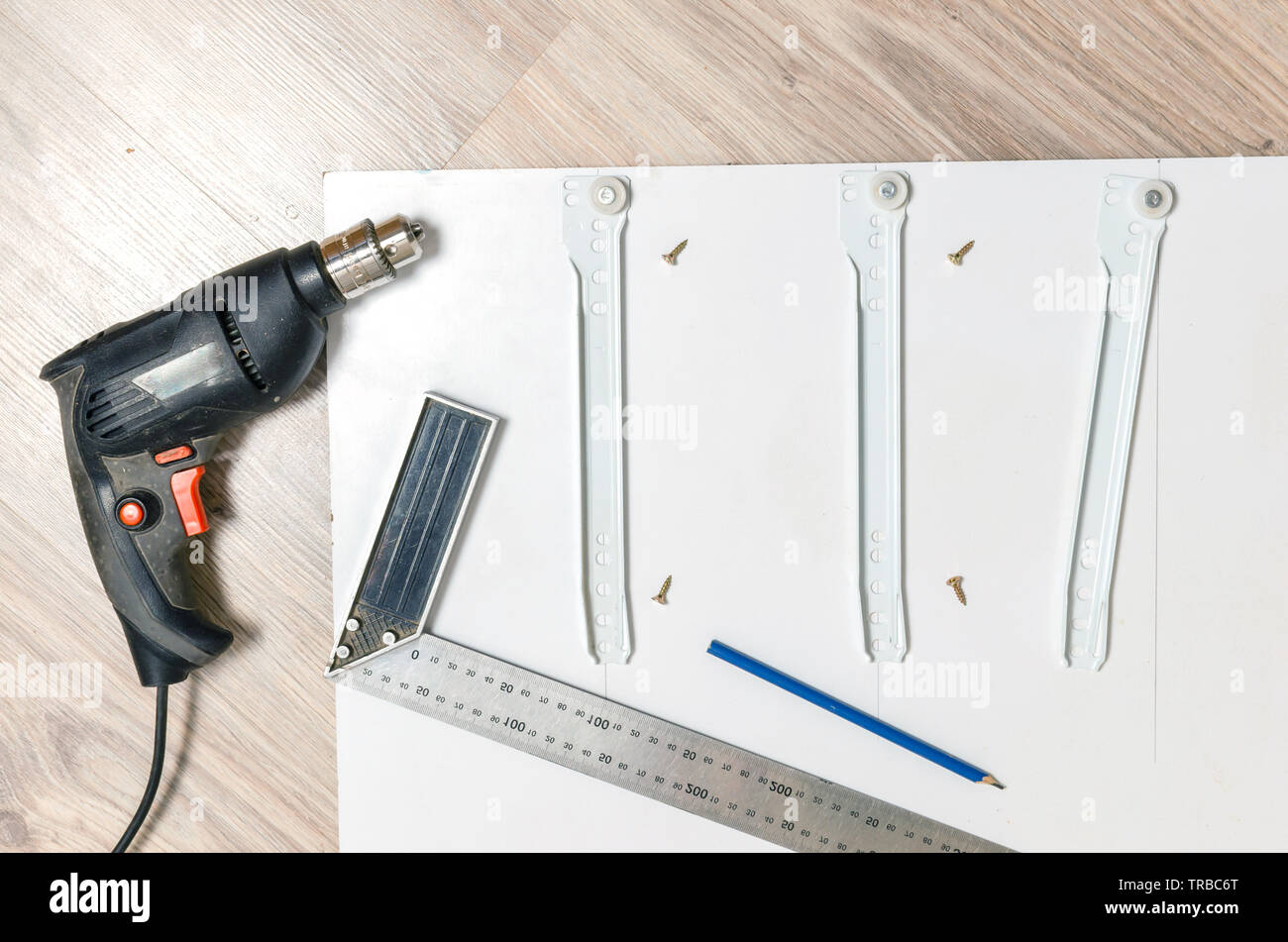 Drill,metallic measuring area, the item of furniture with a stand marked with a pencil furniture guides. - Stock Image