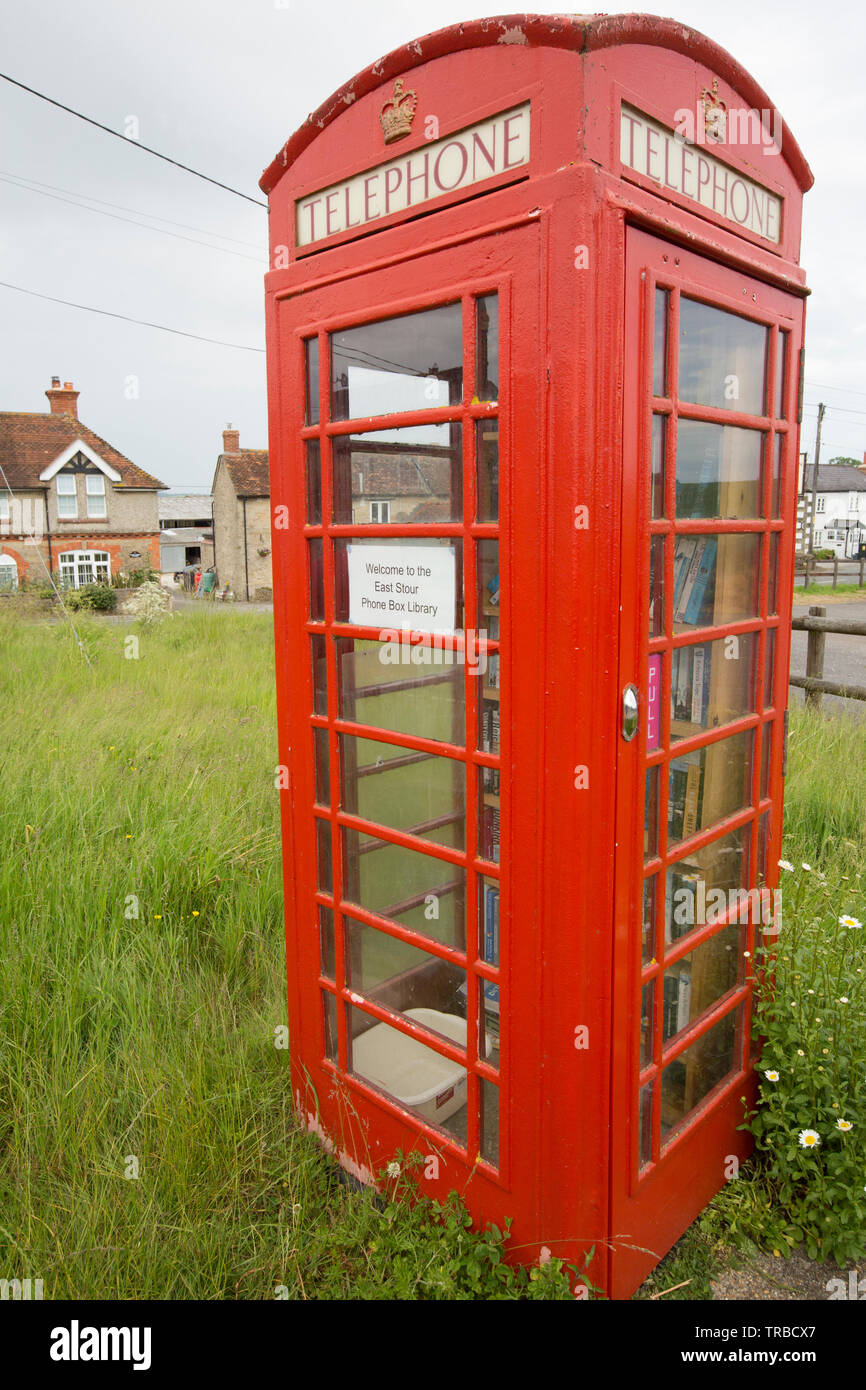 A red telephone box in rural Dorset that has been used as a library. East Stour North Dorset England UK GB - Stock Image