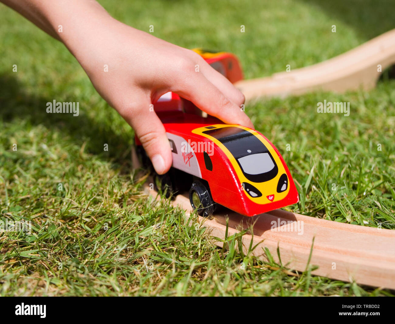 Child Playing with a Wooden Toy Brio-style Virgin Pendolino Train Stock Photo