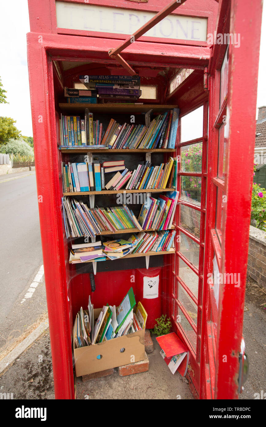 A red telephone box in rural Dorset that has been used as a childrens library. Marnhull North Dorset England UK GB - Stock Image