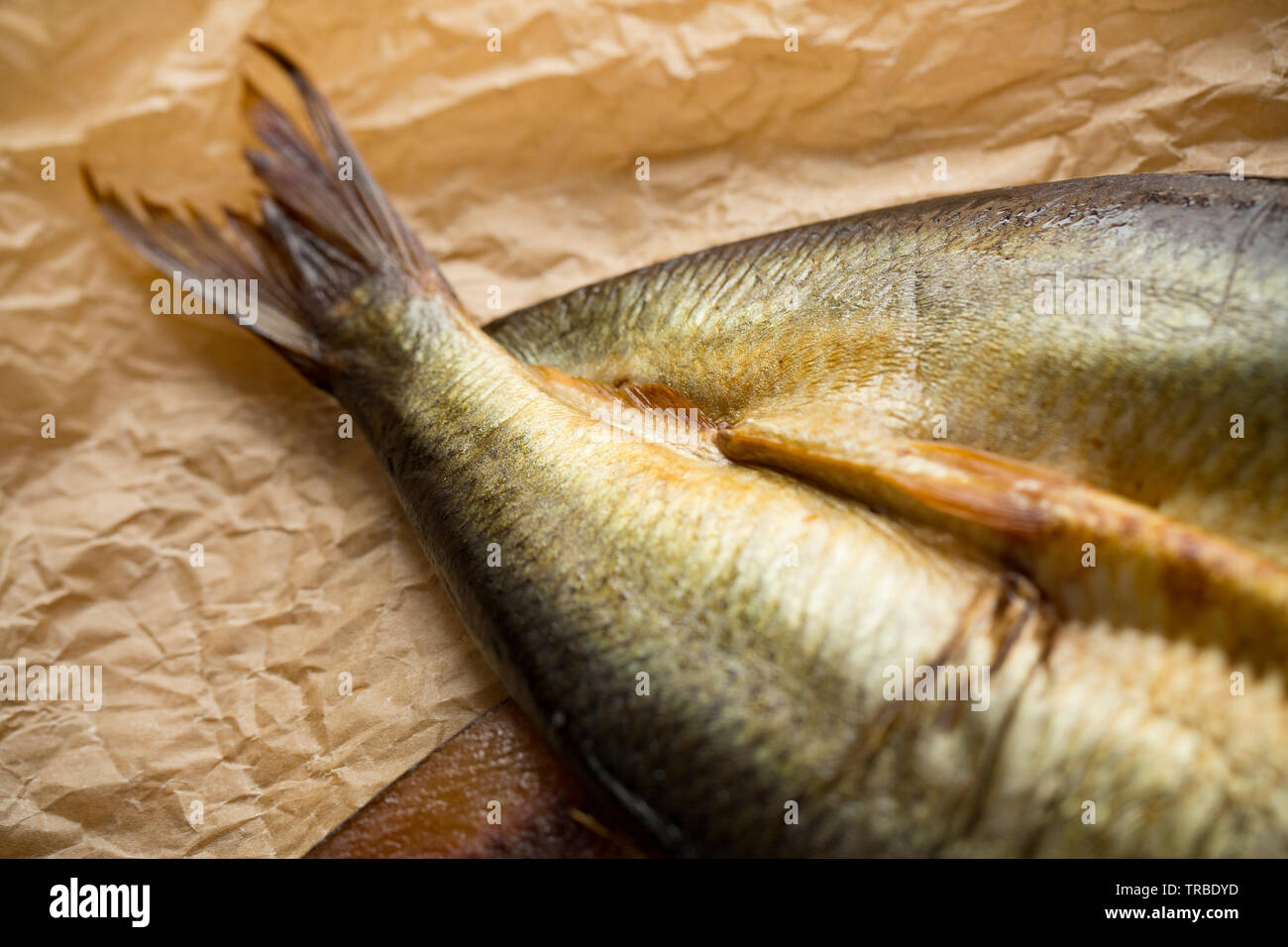 Detail of the tail of a herring, Clupea harengus, that has been split and cold smoked to make a kipper. This is a 'Craster Kipper' and was bought from - Stock Image