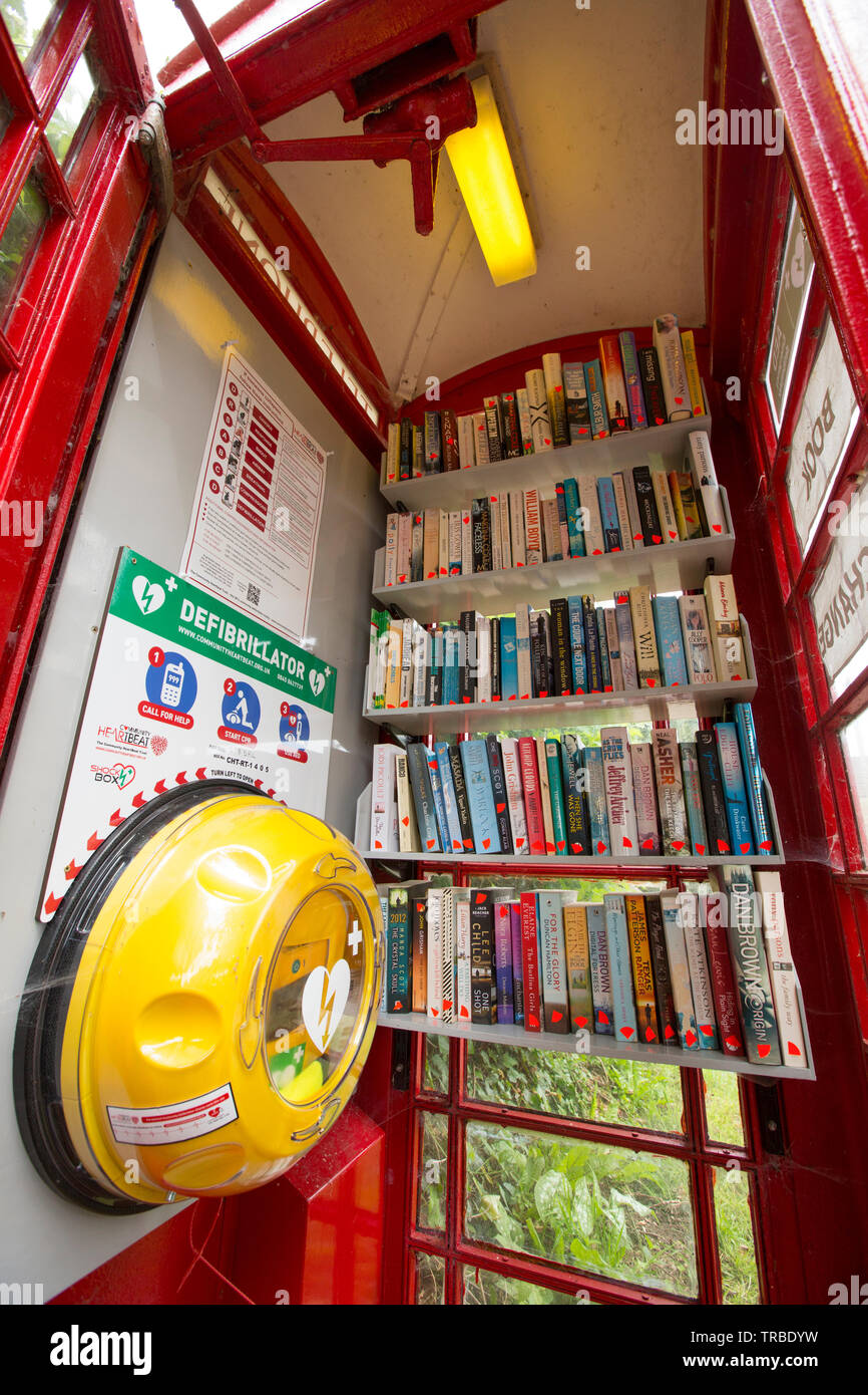 A red telephone box in rural Dorset that has been used as a book exchange. The phone box also houses a defibrillator. West Stour North Dorset England - Stock Image