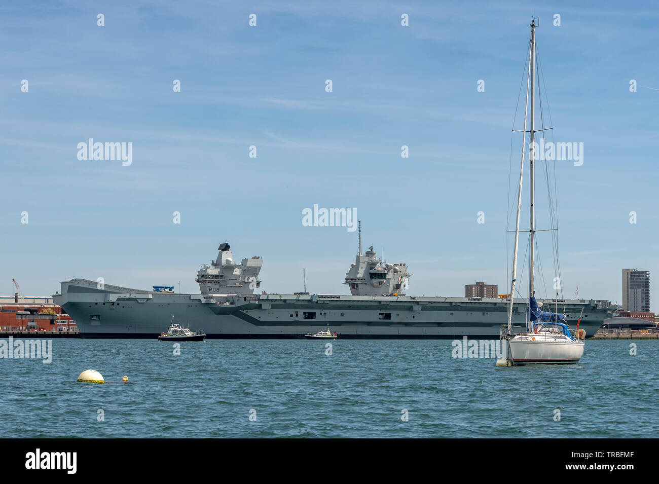 HMS Queen Elizabeth docked in Portsmouth Harbour with police patrol boats - Stock Image