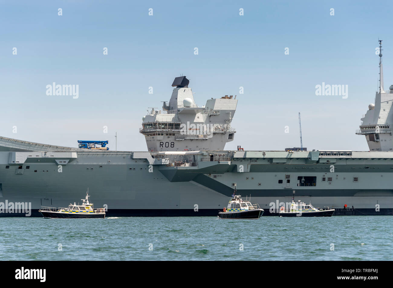 HMS Queen Elizabeth in Portsmouth Harbour with three police boats guarding, ready for Donald Trumps state visit on June 5th 2019 - Stock Image