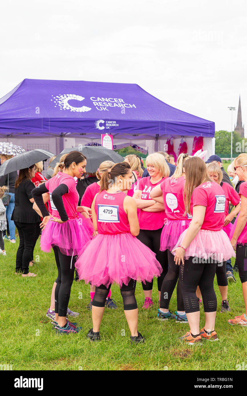 Warrington, UK. 2nd June 2019. Warrington, UK. 2nd June 2019. Race for Life 2019, Warrington, in aid of Cancer Research. A group of women stand talking in front of the Cancer Research tent prior to the start of the race Credit: John Hopkins/Alamy Live News - Stock Image