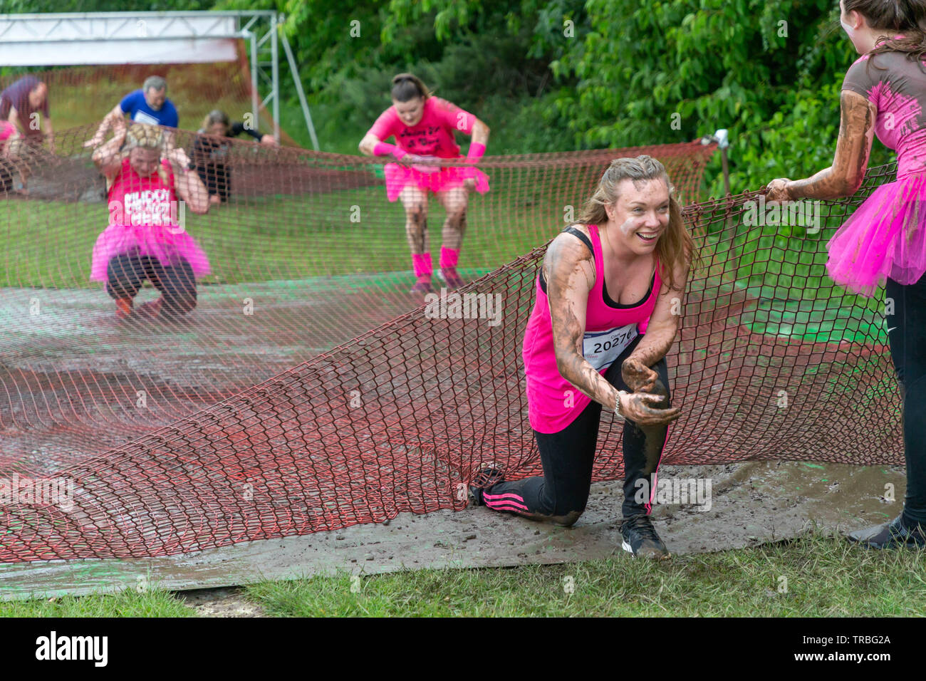 Warrington, UK. 2nd June 2019. Warrington, UK. 2nd June 2019. Race for Life 2019, Warrington, in aid of Cancer Research. Contestants crawl underneath nets as one of their obstacles Credit: John Hopkins/Alamy Live News - Stock Image