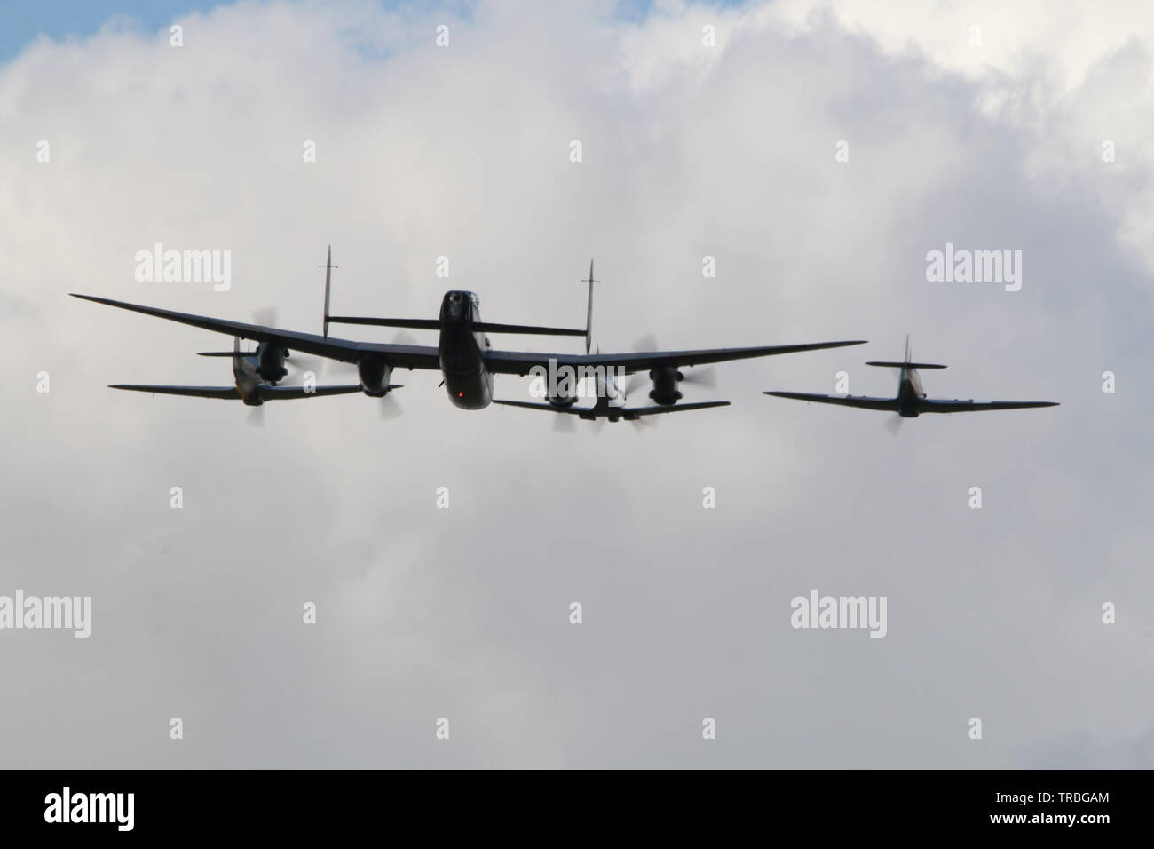Lancaster Bomber , 2 hurricanes & a Spitfire flying formation - Stock Image