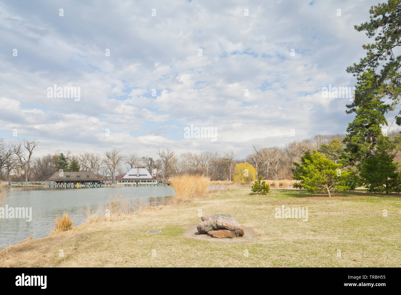 St. Louis Forest Park beside the Post-Dispatch Lake. Rock memorializing the lake, a budding weeping willow, and the Boathouse under partly cloudy sky. - Stock Image