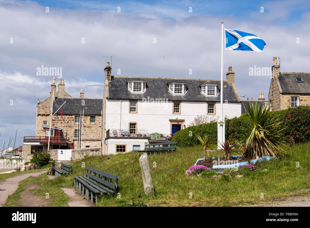 Scottish flag flying outside old buildings in coastal village of Findhorn, Moray, Scotland, UK, Britain Stock Photo