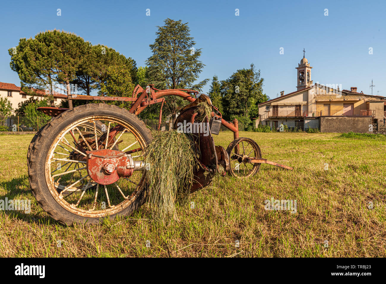 Summer landscape of a meadow with old red plow, detail of hay and bell tower in the background - Stock Image