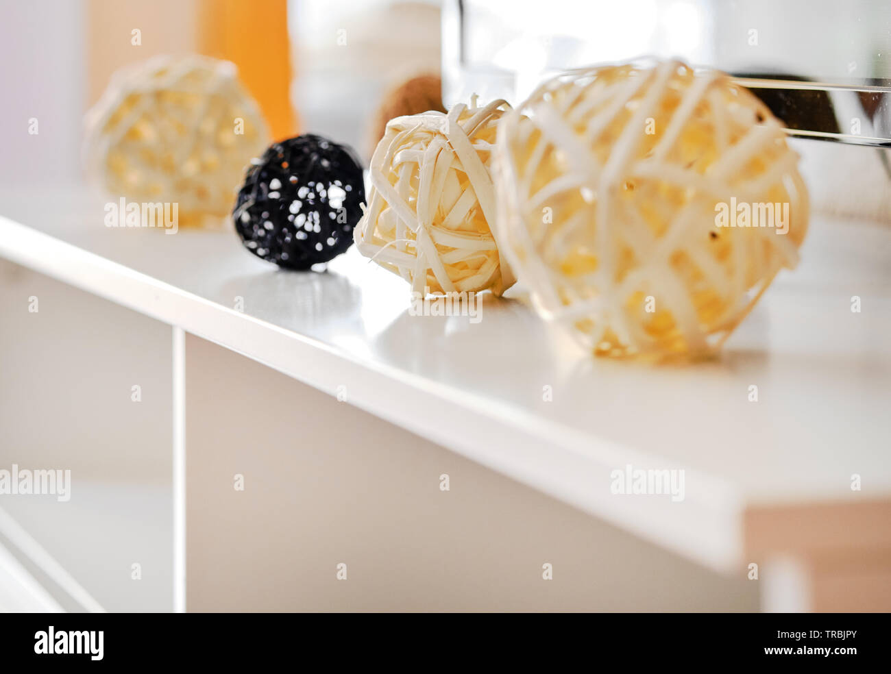 Decorative yellow and black different shapes balls, wicker from natural materials on a white table inside of living room, at home, close up image, no - Stock Image