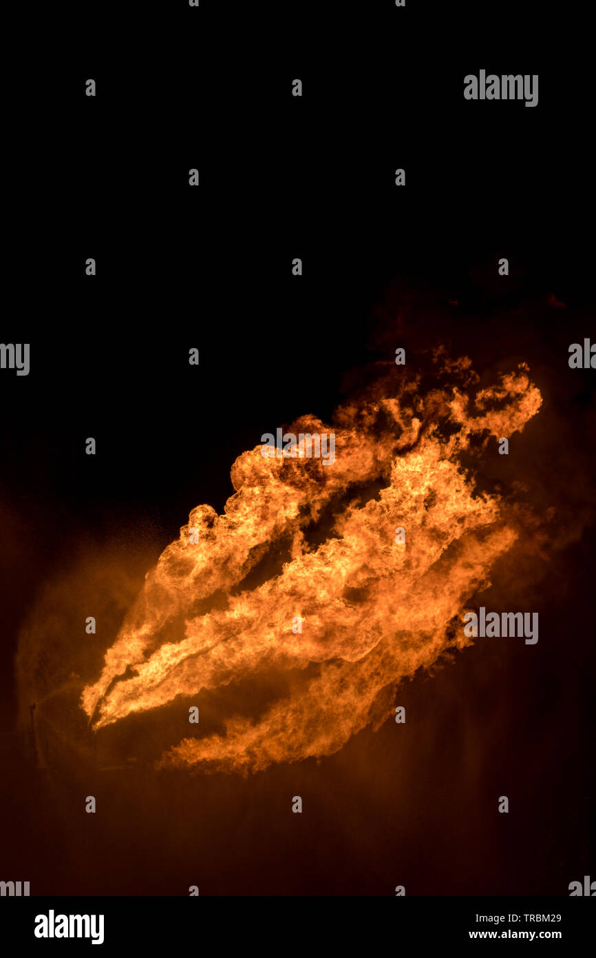 Well testing operation (flaring) of an oil and gas drilling rig. Burning huge gas flame controlled by the deluge system - Stock Image