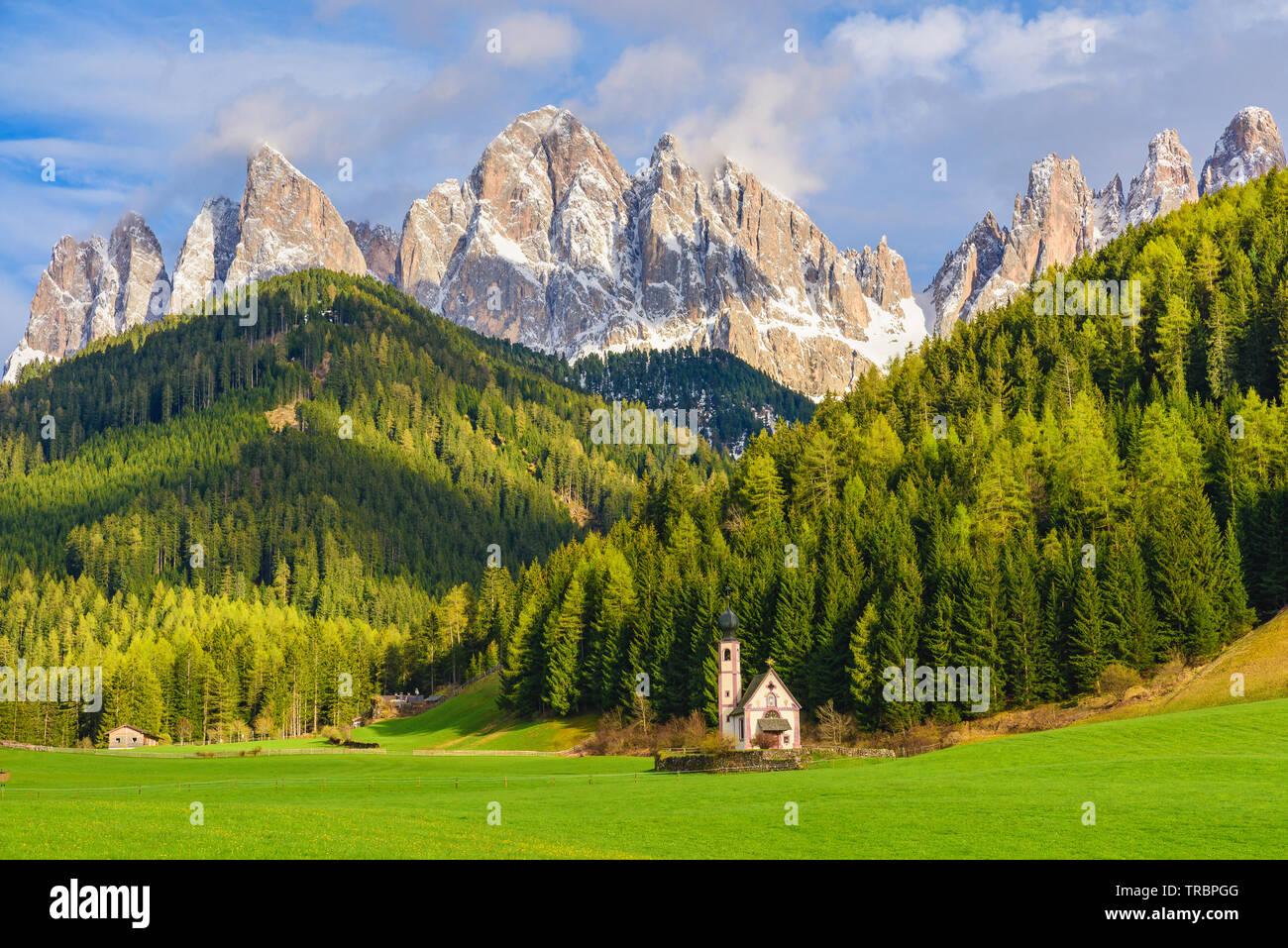Sunny landscape of Dolomite Alps. St Johann Church with beautiful Dolomiti mountains, Santa Maddalena, Val Di Funes, Dolomites, Italy. - Stock Image