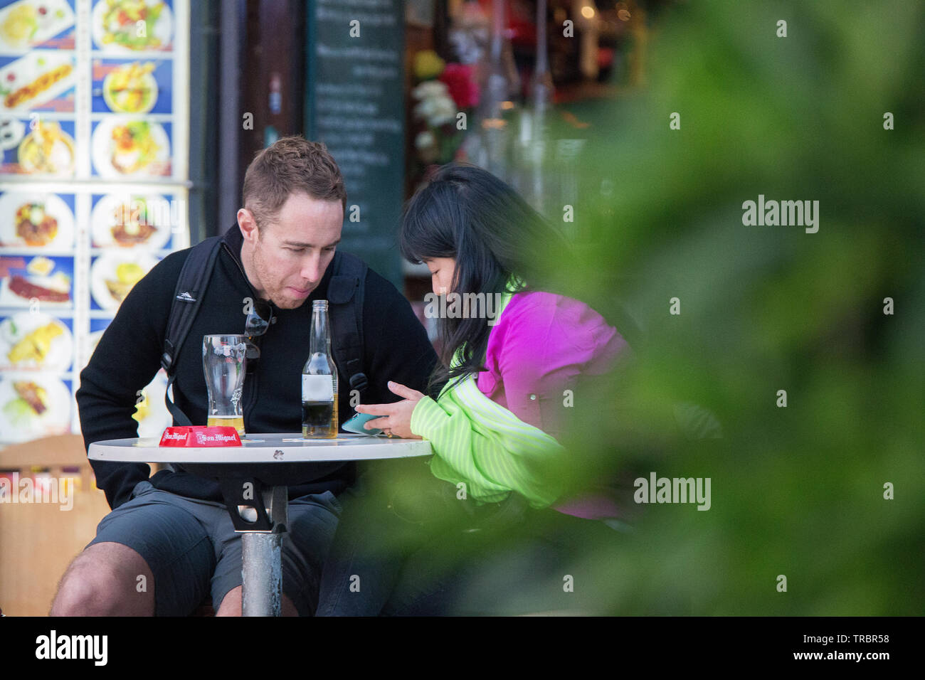 01/25/2015 Europen Man and chinese  girl talking to each other  and  lookimg into a smartphone  and  drinking  beer - Stock Image
