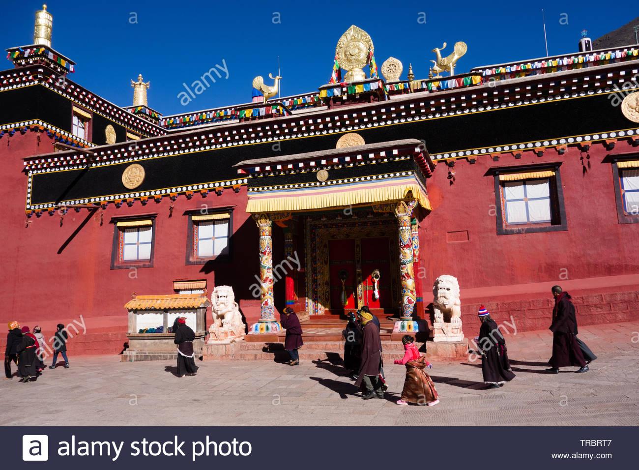 Tibetan pilgrims walk around Bakong Monastery, Dege, Sichuan, China - Stock Image