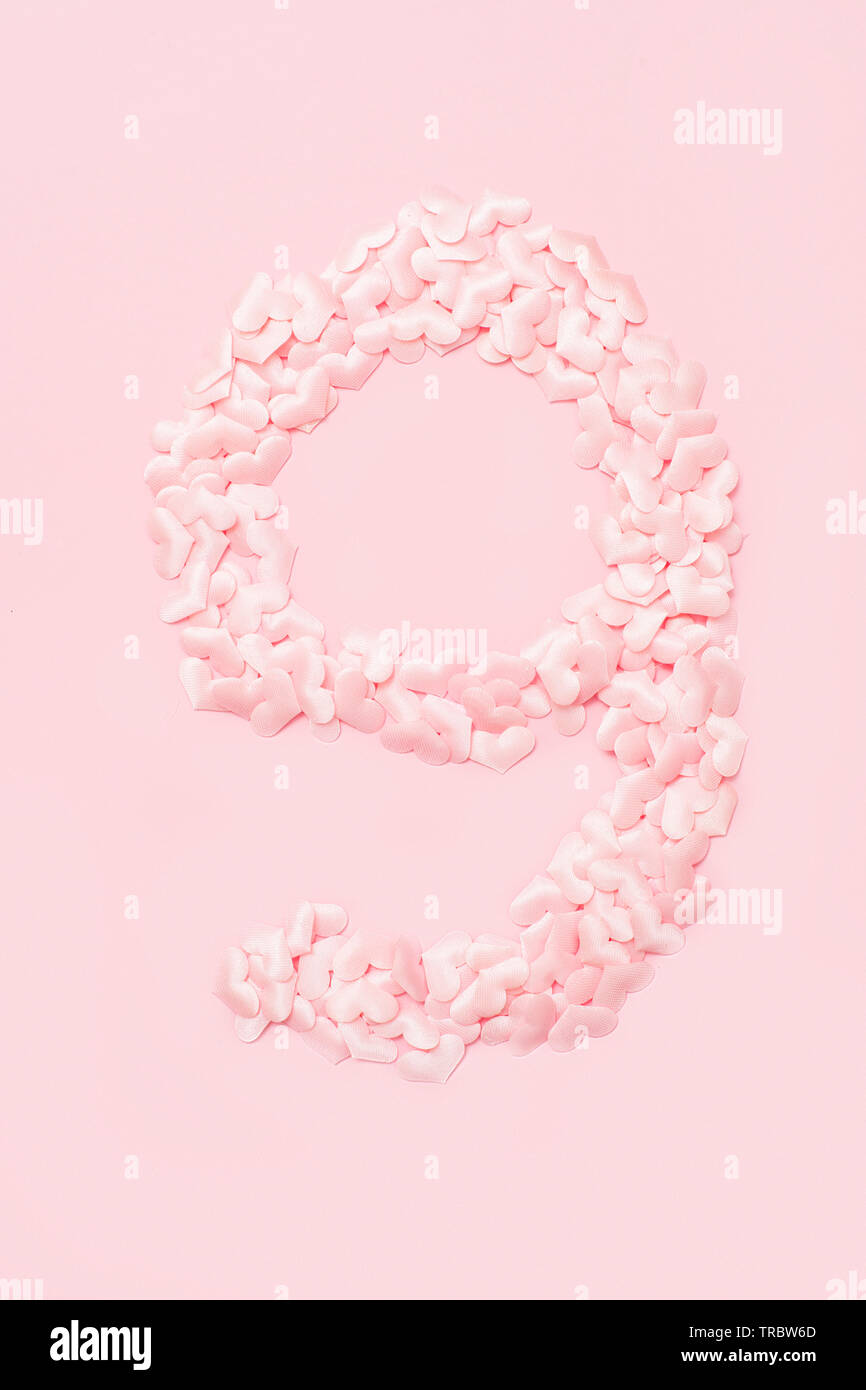 Number nine collected from decorative pink hearts. Isolated on pink background - Stock Image