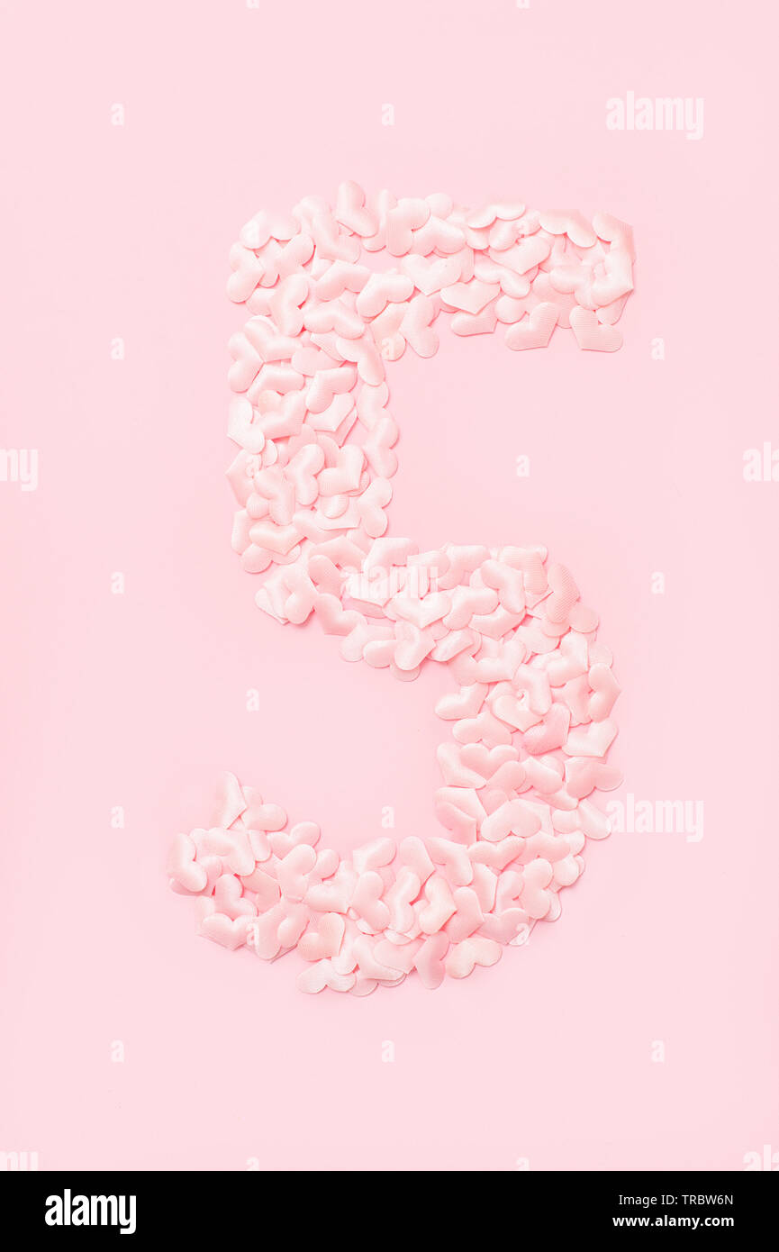 Number five collected from decorative pink hearts. Isolated on pink background - Stock Image