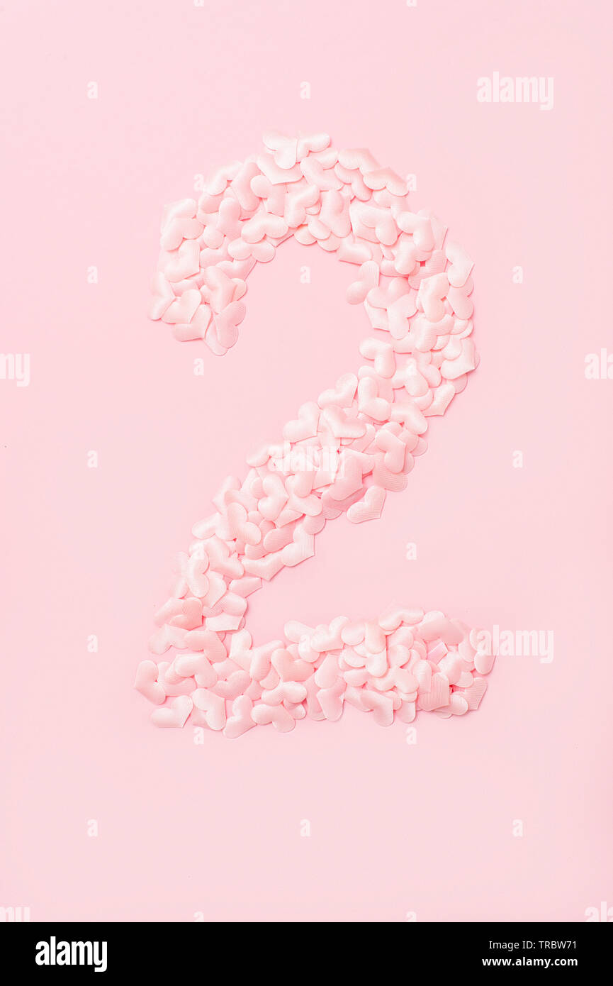 Number two collected from decorative pink hearts. Isolated on pink background - Stock Image