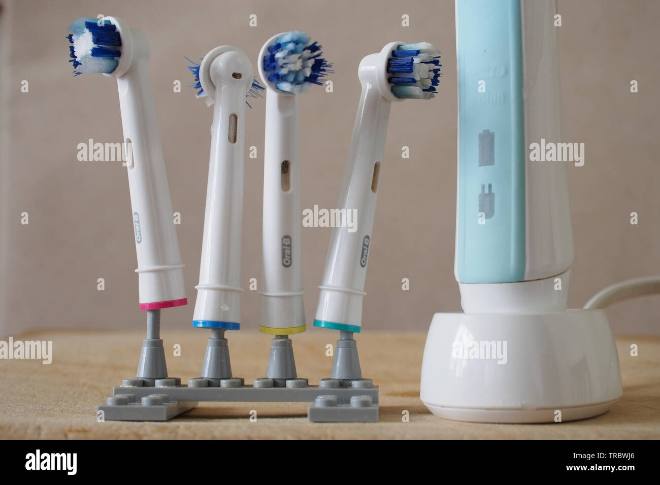 Four well-used electric toothbrush heads on a home-made Lego stand, next to a Braun electric toothbrush on its wireless rechargeable base. - Stock Image