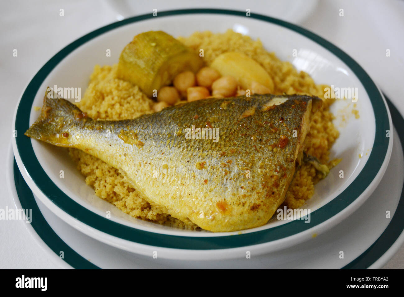 A traditional North African dish of couscous with fish (sea bream), chickpeas and vegetables, served at a restaurant in the medina of Tunis, Tunisia. Stock Photo