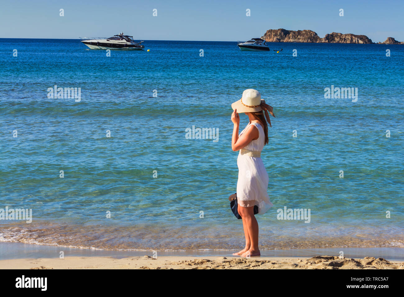 Young trendy woman relax on the beach. Happy island lifestyle. Holiday in paradise. In Hindergrund beach blue sky, crystal clear sea and two luxury mo - Stock Image